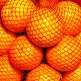 Bunch of fresh  Orange fruits in a string bag on market. Fruit b Royalty Free Stock Image