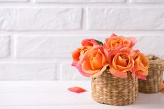 Bunch of fresh orange roses  on white wooden background against. White wall. Place for text. Floral still life Royalty Free Stock Image