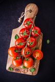A bunch of fresh organic cherry tomatoes in olive cutting board Stock Photos