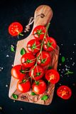 A bunch of fresh organic cherry tomatoes with sea salt and basil in olive cutting board. A bunch of fresh organic cherry tomatoes with sea salt and basil on a Stock Image