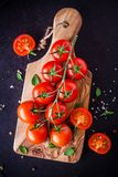 A bunch of fresh organic cherry tomatoes with sea salt and basil in olive cutting board Stock Photo