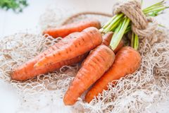 Bunch of Fresh organic dirty carrots from farm market on the white wooden background. Vegetables. Healthy food concept. Vegetarian Stock Photos