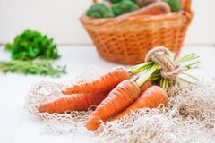 Bunch of Fresh organic dirty carrots from farm market on the white wooden background. Vegetables. Healthy food concept. Vegetarian Stock Photo