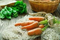 Bunch of Fresh organic dirty carrots and other purchased products from farm market on the wooden background. Vegetables. Healthy d Royalty Free Stock Image