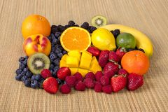 Fresh Organic Fruits And Berries On A Bamboo Background. A bunch of fresh, organic fruits and berries on a bamboo background stock photography