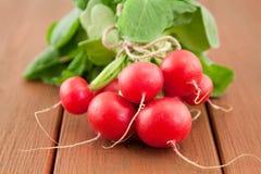 Bunch of fresh organic radish. Bunch of fresh red organic radish on wooden background Royalty Free Stock Image