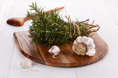 Bunch of fresh organic rosemary and garlic on chopping board. Freshly harvested bunch of rosemary tied up with thread and garlic on a chopping board on white royalty free stock photography
