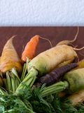 Bunch of fresh picked rainbow carrots on cutting board stock images