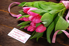 Bunch of fresh pink tulips and card with greetings Stock Photography