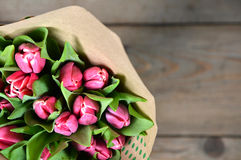 Bunch of fresh purple pink tulip flowers close up composition on. Wood rustic background Royalty Free Stock Image