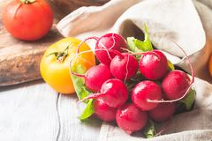 Bunch of fresh radish on dark boards, closeup. Large bunch of fresh radish on white wooden table, closeup Stock Image