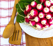 Bunch of fresh radish on white plate closeup, wooden background. Red natural european radishes. Freshly harvested organic vegetables Stock Images