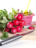 Bunch of fresh radishes. Being sliced thinly for use in a salad with a sharp steel knife Royalty Free Stock Images