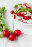 Bunch of fresh radishes and salad on a plate. Closeup Stock Photo