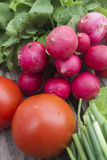 Bunch of fresh radishes and tomato. On wooden board Stock Photo