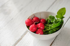Bunch of fresh radishes in white bowl on white board Royalty Free Stock Photography