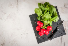 Bunch of fresh radishes. On a white concrete table, on a slate board with a knife, top view, copy space Stock Photos