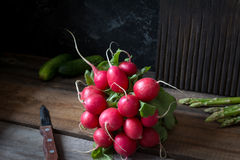 Bunch of fresh radishes on wooden table. Fresh radishes on rustic wooden table, natural light, selective focus Stock Images