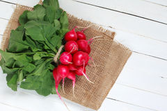 Bunch of fresh radishes on wooden table. Spring vegetables. A bouquet of fresh radish on a wooden table Stock Photo