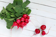 Bunch of fresh radishes on wooden table Stock Images
