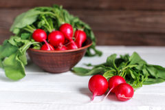 Bunch of fresh radishes on wooden table. Spring vegetables. A bouquet of fresh radish on a wooden table Stock Image