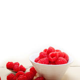 Bunch of fresh raspberry on a bowl and white table Royalty Free Stock Images