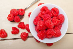 Bunch of fresh raspberry on a bowl and white table Stock Image