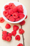 Bunch of fresh raspberry on a bowl and white table Stock Photos