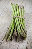 Bunch of fresh raw garden asparagus on rustic wooden table background. Green spring vegetables stock images