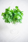 Bunch of fresh raw green parsley. In a glass view from the top selective focus vertical frame Stock Photography