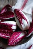 Red italian chicory. A bunch of fresh raw red italian chicory on a white linen dishcloth Royalty Free Stock Image