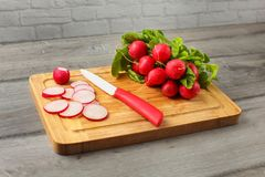 Bunch of fresh red radish on a wooden cutting board, ceramic kni. Fe, with some of radish cut in small circles Royalty Free Stock Images