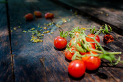 A bunch of fresh red tomatoes On the old dark wooden floor Royalty Free Stock Photography