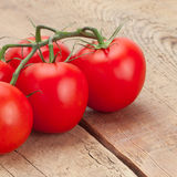 Bunch of fresh red tomatoes on wooden table - studio shot Stock Photo