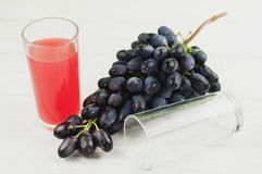 Bunch of fresh ripe blue grapes near transparent and fragile glass full of juice beside empty glass on old wooden planks. Bunch of fresh ripe blue grapes near royalty free stock photography