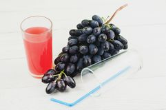 Bunch of fresh ripe blue grapes near transparent and fragile glass full of juice beside empty glass with plastic tubule. On old wooden rustic white planks stock photography