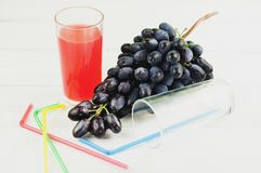 Bunch of fresh ripe blue grapes near transparent and fragile glass full of juice beside empty glass with plastic tubule. And heap of colored tubules on old royalty free stock images