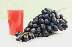 Bunch of fresh ripe blue grapes near transparent and fragile glass full of juice on old wooden white planks. Bunch of fresh ripe blue grapes near transparent and stock photos
