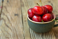 Bunch of fresh ripe colorful glossy sweet cherries in ceramic tea cup on wood background, minimalist, copy space for text Stock Image