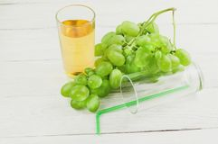 Bunch of fresh ripe green grapes near transparent and fragile glass full of juice beside empty glass with plastic tubule on planks. Bunch of fresh ripe green royalty free stock images
