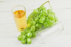 Bunch of fresh ripe green grapes near transparent and fragile glass full of juice beside empty glass on old wooden rustic planks. Bunch of fresh ripe green stock photo
