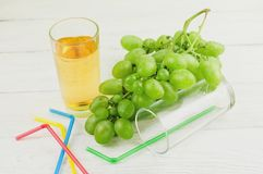 Bunch of fresh ripe green grapes near transparent and fragile glass full of juice beside empty glass with plastic tubule. And heap of colored tubules on old royalty free stock image