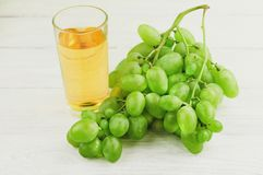 Bunch of fresh ripe green grapes near transparent and fragile glass full of juice on old wooden white planks. Bunch of fresh ripe green grapes near transparent royalty free stock image