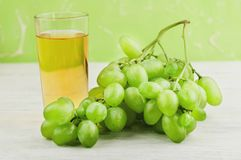 Bunch of fresh ripe green grapes near transparent and fragile glass full of juice on old wooden white planks. Bunch of fresh ripe green grapes near transparent stock photos
