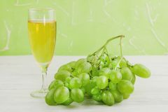 Bunch of fresh ripe green grapes near transparent and fragile glass full of wine on old wooden white planks. Bunch of fresh ripe green grapes near transparent royalty free stock image