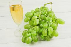 Bunch of fresh ripe green grapes near transparent and fragile glass full of wine on old wooden white planks. Bunch of fresh ripe green grapes near transparent royalty free stock photography