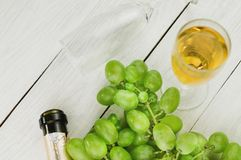 Bunch of fresh ripe green grapes near transparent and fragile glass full of wine and one opened bottle near empty glass on woo. Bunch of fresh ripe green grapes stock photos