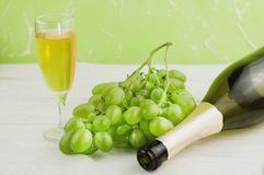 Bunch of fresh ripe green grapes near transparent and fragile glass full of wine and one opened bottle on old wooden planks. Bunch of fresh ripe green grapes stock photos