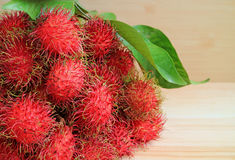 Bunch of Fresh Ripe Rambutan Fruits with Green Leaves on the Wooden Table. Background Stock Images