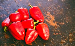 Bunch of fresh ripe red bell peppers on an old black wood grunge background Stock Images